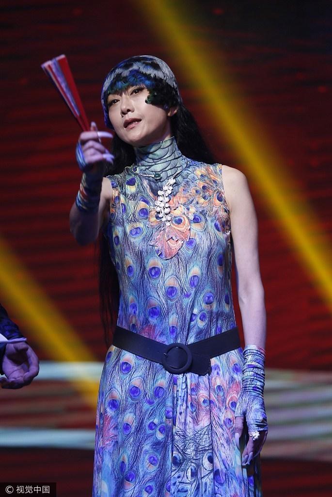 杨丽萍穿孔雀服与安保合影 长指甲抢镜
